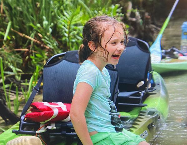Child sitting on kayak and smiling