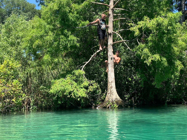 Two people on tree in river Weeki Wachee